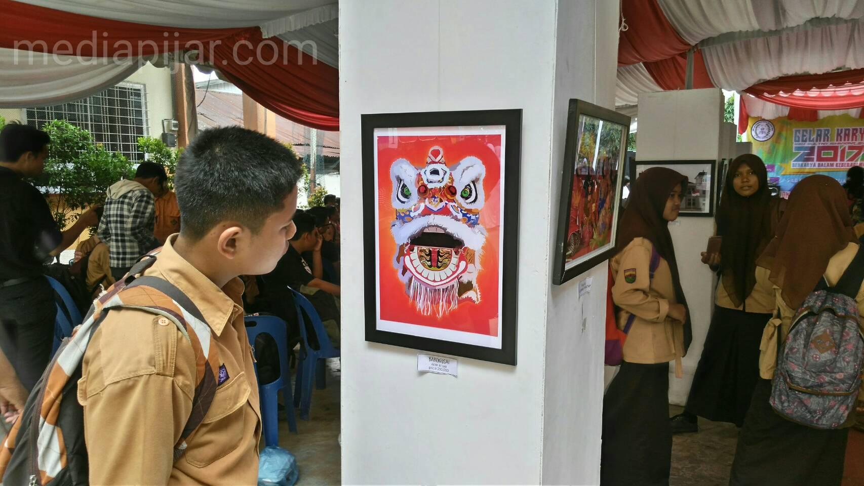 Seorang siswa sedang memandang karya seni dalam pameran kegiatan gelar karya SMK Sultan Iskandar Muda, Sabtu (11/2). Fotografer : Muhammad Kurniawan