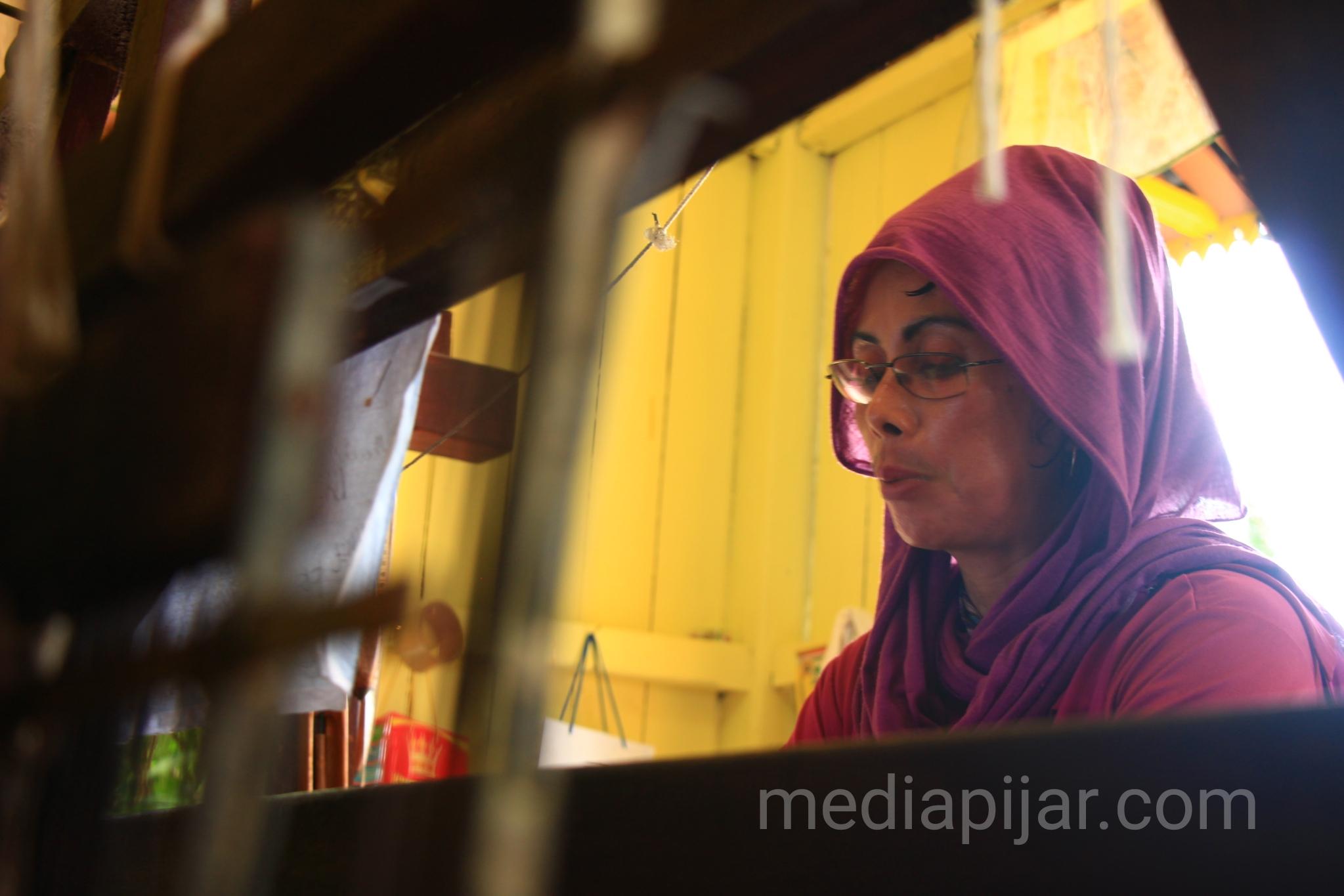 Penenun di Rumah Tenun Senapelan masih menggunakam mesin tenun manual.  (Fotografer: Hidayat Sikumbang)