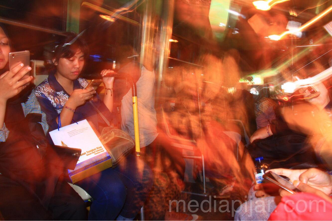 """""""Setiap orang mempunyai caranya masing-masing dalam menikmati suasana bis kota. Media sosial tetap menjadi pilihan pertama, kepala tertunduk menatap layar"""" (Fotografer: Hidayat Sikumbang)"""